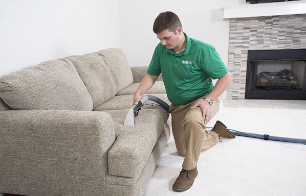 technician cleaning a couch
